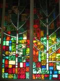 Summer season in stained glass along the wall of the chapel.